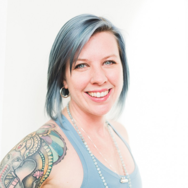 Beautiful smile and Ganesh Tattoo on Katie Thorne yoga teacher posing for headshot at ashtanga yoga victoria photoshoot