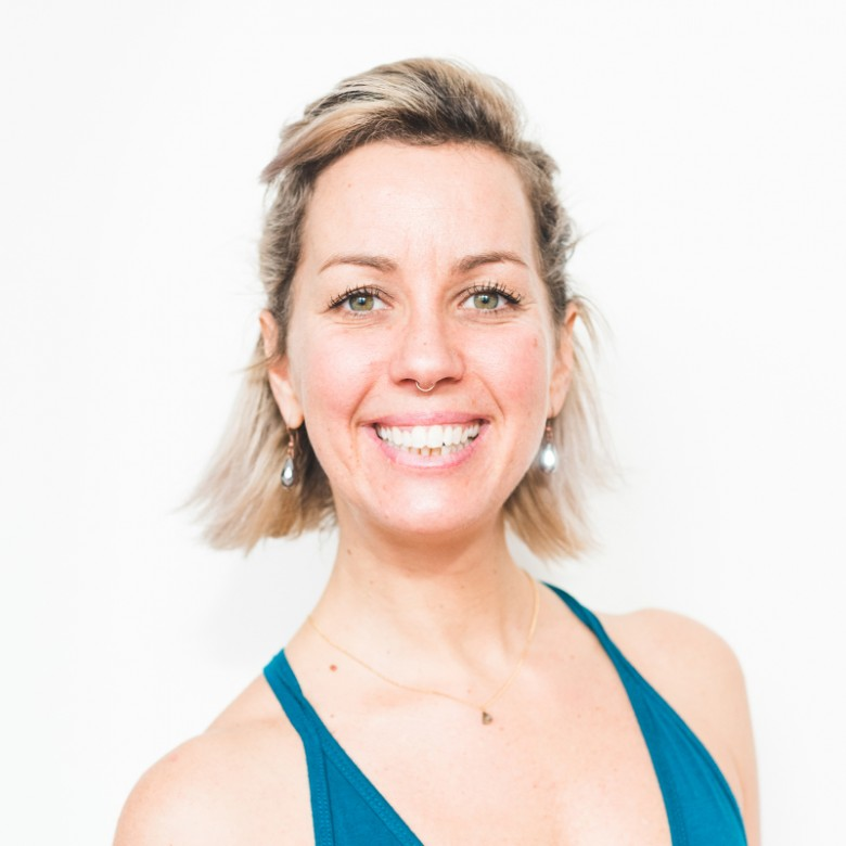 Big smile and blue shirt on Kimber Allan posing for headshot at ashtanga yoga victoria photoshoot